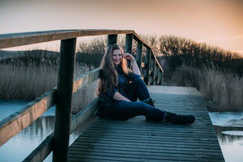 Milena, Fotografin von PhotoGravity, lächelnd auf einer Brücke sitzend
